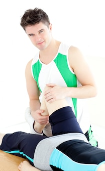 Młody męski fizyczny terapeuta sprawdza kobiety kolano