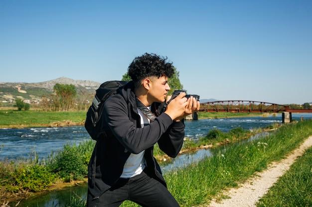 Młody męski fotograf fotografuje naturę w letnim dniu