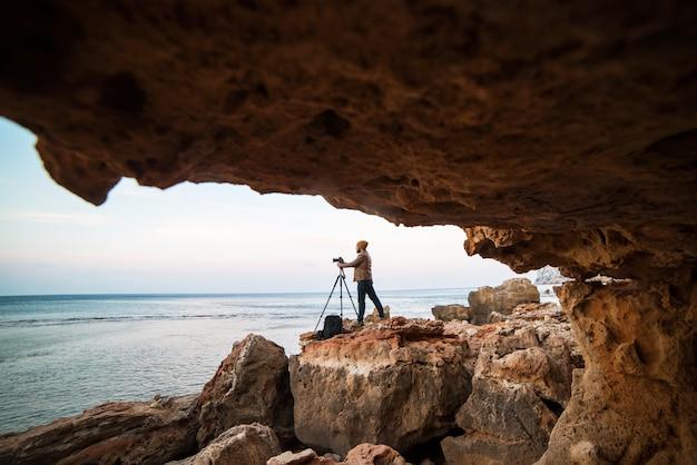 Młody męski fotograf stojący w ustach skalnej jaskini ze statywem i robienia zdjęć