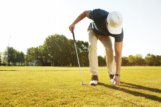 Młody męski golfista umieszcza piłkę golfową na trójniku