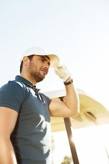 Młody męski golfista w kapeluszu