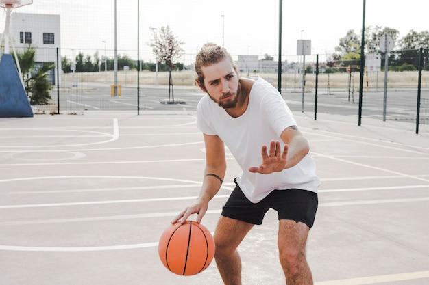 Młody męski gracz koszykówki w akci