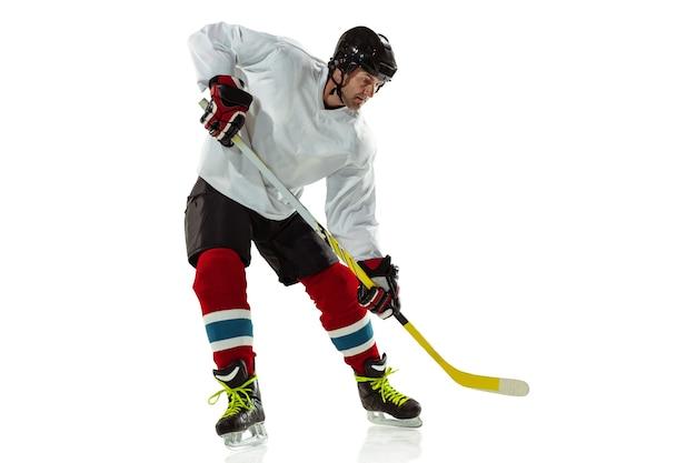 Młody męski gracz w hokeja z kijem na boisku i białej ścianie. uprawiający sportowiec w sprzęcie i kasku