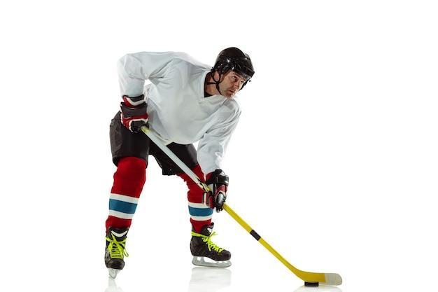 Młody męski gracz w hokeja z kijem na boisku i białej ścianie