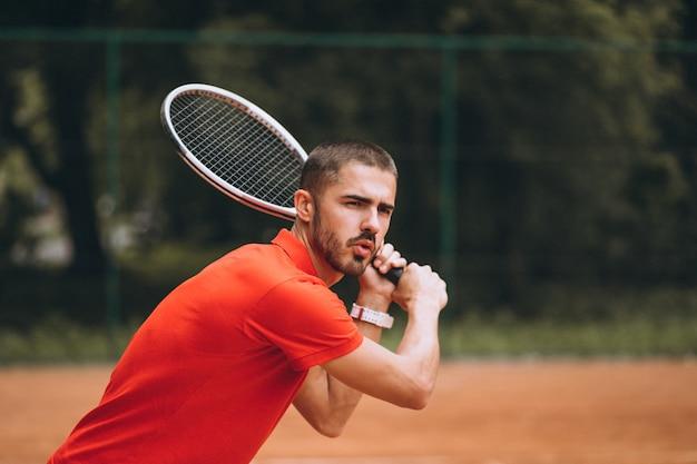 Młody męski gracz w tenisa przy sądem