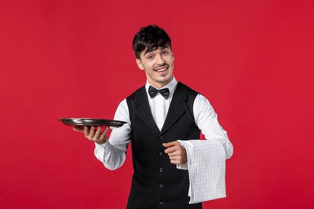 Młody męski kelner w mundurze z motylem na szyi i trzymającym ręcznik na czerwonym tle