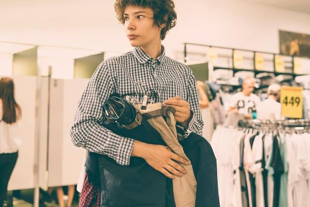 Młody męski nastolatka odprowadzenie w przypadkowych ubrań sklepu zakupy pojęciu