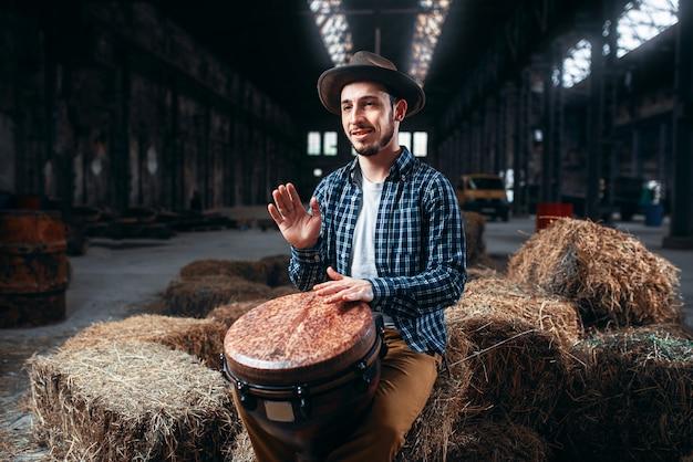 Młody męski perkusista przeciwko afrykańskiemu bębenkowi drewnianemu