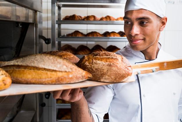 Młody męski piekarz wyjmuje z drewnianą łopatą świeżo piec chleb z piekarnika