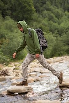 Młody męski podróżnik cieszący się wiejskim otoczeniem