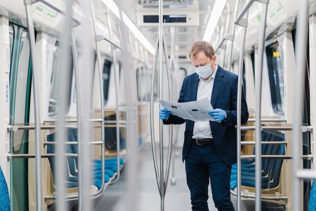 Młody męski przedsiębiorca nosi jednorazową maskę medyczną i rękawiczki w metrze, zapobiega chorobie wieńcowej, stawia w pustej karetce, czyta gazetę, dowiaduje się o wirusie zakaźnym