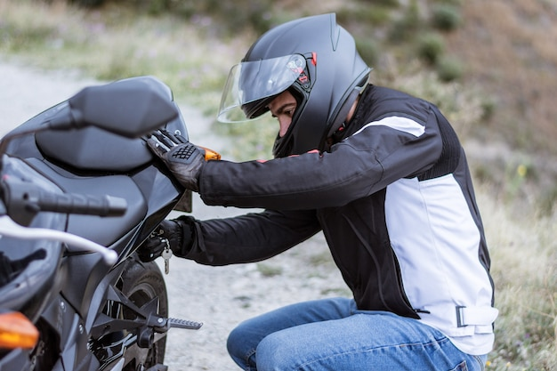 Młody męski rowerzysta sprawdza jego motocykl przed jechać nim