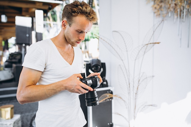 Młody męski ślubny fotograf pracuje