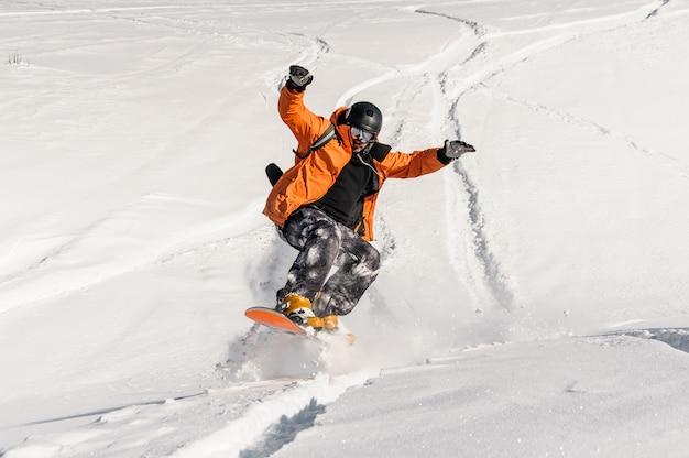 Młody męski snowboarder w pomarańczowej odzieży sportowej, skoki na stoku śniegu