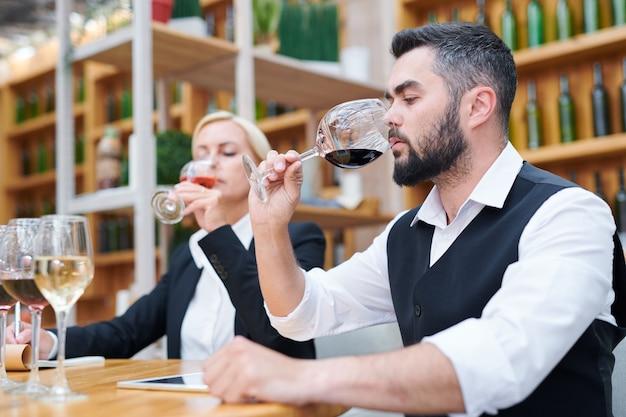 Młody męski sommelier wąchający czerwone wino w bokal ze swoim napojem degustacyjnym coleague