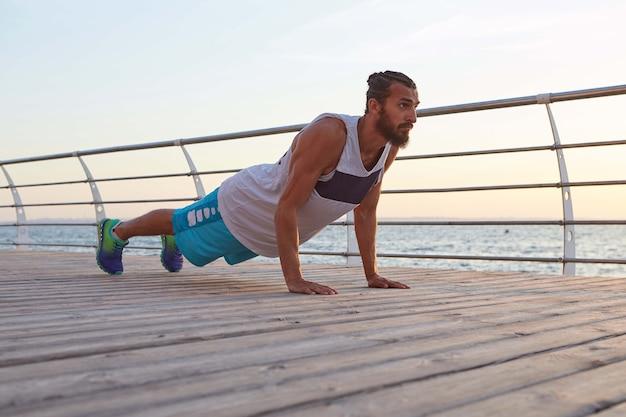 Młody męski, sportowy brodaty facet robi poranne ćwiczenia nad morzem, rozgrzewkę po bieganiu i robieniu pompek, trzyma deskę.