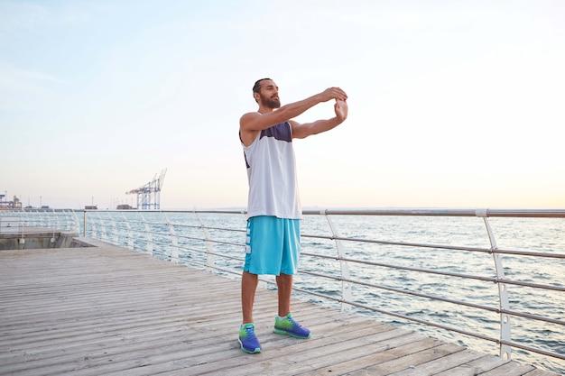 Młody męski, sportowy brodaty facet robi stretching, poranne ćwiczenia nad morzem, rozgrzewkę po bieganiu.