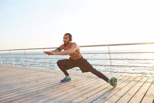 Młody męski, sportowy brodaty facet uprawia rozciąganie, słuchanie ulubionej muzyki na słuchawkach, poranne ćwiczenia nad morzem, rozgrzewka po biegu, prowadzi zdrowy, aktywny tryb życia. męski model fitness.
