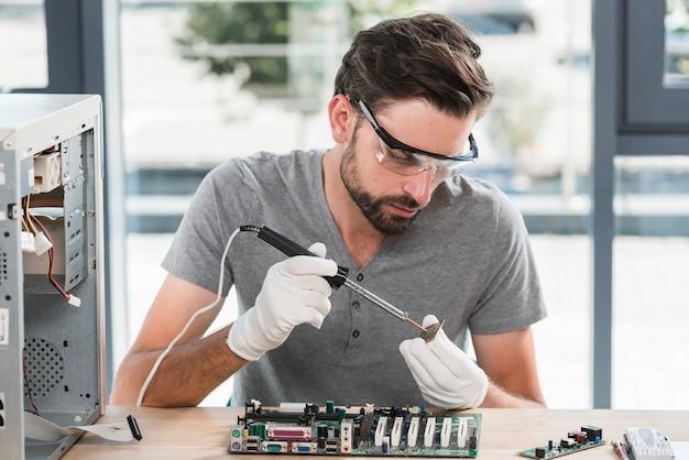 Młody męski technik pracuje na komputerowym ram