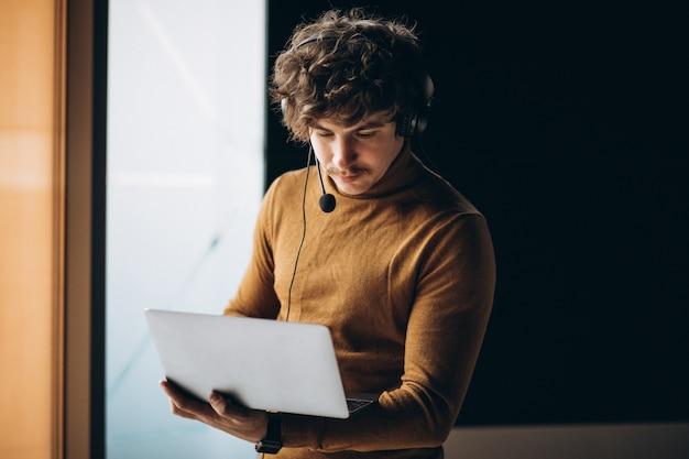 Młody męski tłumacz pracuje na laptopie