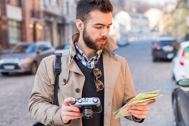 Młody męski turystyczny patrzeć drogę z mapą w jego ręce w mieście