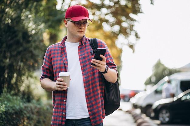 Młody męski uczeń pije kawę używać telefon w parku