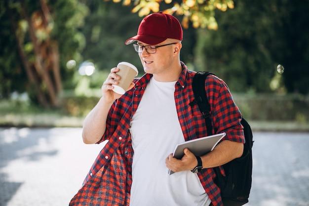 Młody męski uczeń pije kawę z laptopem w parku