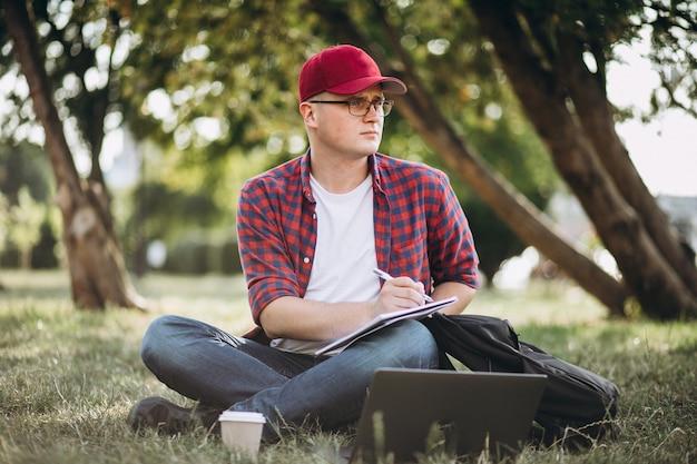 Młody męski uczeń pracuje na komputerze w parku