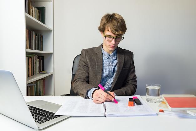 Młody męski uczeń pracuje z książkami i laptopem przy domowym przydziałem lub projektem