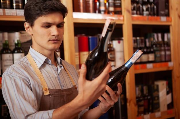 Młody męski winiarz pracuje przy jego sklepem, trzyma dwa wino butelki, kopii przestrzeń