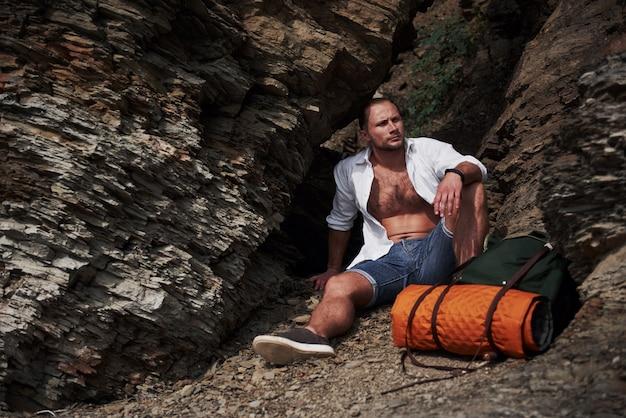 Młody męski wycieczkowicz relaksuje na skalistym masywie z spokojnym lato zmierzchem z plecakiem. podróż wakacje koncepcja przygoda wakacje