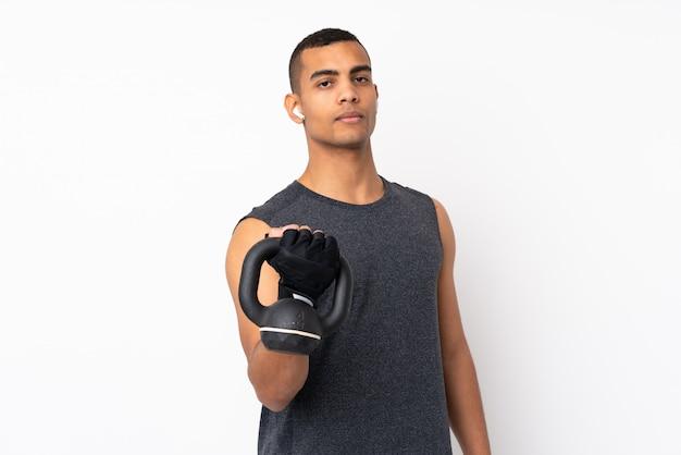 Młody mężczyzna african american sportu na pojedyncze białej ścianie co w podnoszeniu ciężarów z kettlebell