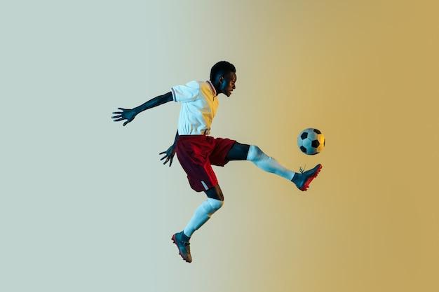 Młody mężczyzna afro-amerykański piłkarz lub piłkarz w odzieży sportowej i butach kopiąc piłkę do celu w skoku w świetle neonowym na gradientowym tle. pojęcie zdrowego stylu życia, sportu zawodowego.