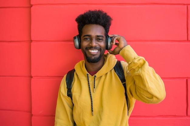 Młody mężczyzna afro słuchanie muzyki w słuchawkach