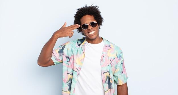 Młody mężczyzna afro szuka nieszczęśliwego i zestresowanego, samobójczy gest robi znak pistoletu ręką, wskazując na głowę