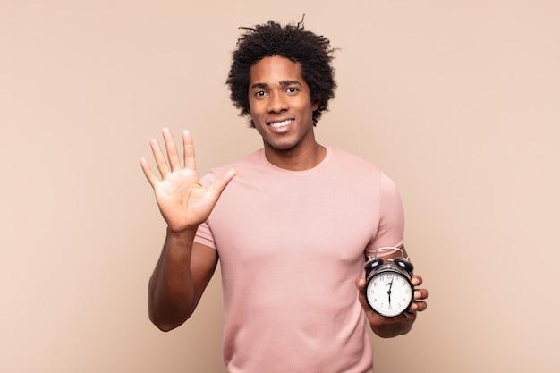 Młody mężczyzna afro uśmiechnięty i wyglądający przyjaźnie, pokazujący numer pięć lub piąty z ręką do przodu, odliczający