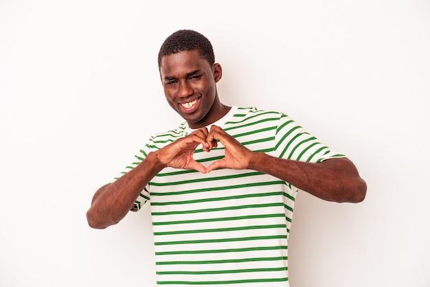 Młody mężczyzna afroamerykanów na białym tle uśmiecha się i pokazuje kształt serca rękami.