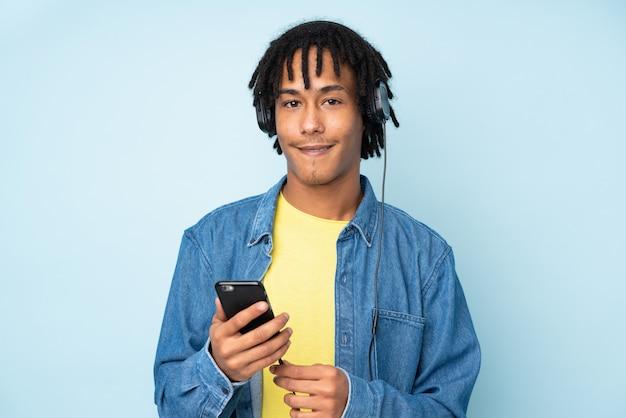 Młody mężczyzna afroamerykanów na niebieską ścianą słuchania muzyki z telefonu komórkowego i patrząc z przodu