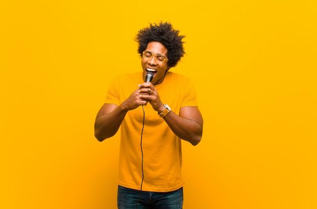 Młody mężczyzna afroamerykanów z mikrofonem śpiewa przeciwko lub