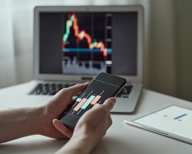 Młody mężczyzna akcjonariusz korzystający z aplikacji biznesowej telefonu komórkowego i kupujący akcje na komputerze