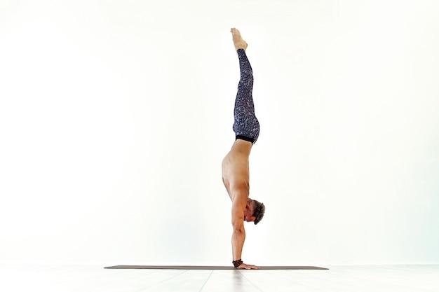 Młody mężczyzna akrobatyka gimnastyczna robi studio stojące na rękach na białym atletycznym sportowcu