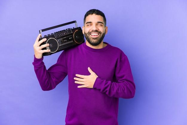 Młody mężczyzna arabian gospodarstwa kasety radiowej izolowane młody mężczyzna arabian słuchania muzyki śmieje się głośno, trzymając rękę na piersi.
