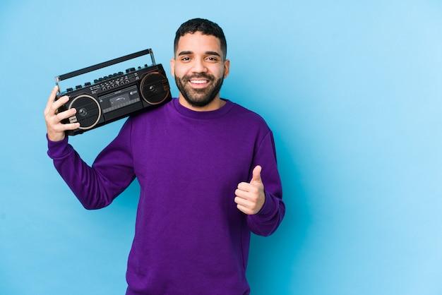 Młody mężczyzna arabian gospodarstwa kasety radiowej izolowane młody mężczyzna arabian słuchania muzyki uśmiecha się i podnoszenie kciuka do góry