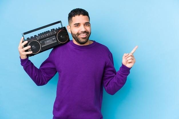 Młody mężczyzna arabian gospodarstwa kasety radiowej izolowane młody mężczyzna arabian słuchania muzyki uśmiecha się i wskazując na bok, pokazując coś w pustej przestrzeni.