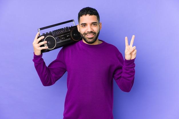 Młody mężczyzna arabian gospodarstwa kasety radiowej izolowane młody mężczyzna arabian słuchania muzyki wykazujące numer dwa palcami.