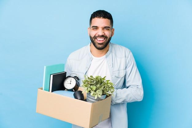 Młody mężczyzna arabian przeprowadzki do nowego domu na białym tle śmiejąc się i dobrze się bawiąc.