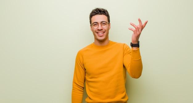 Młody mężczyzna arabski czuje się szczęśliwy, zaskoczony i wesoły, uśmiechając się z pozytywnym nastawieniem, realizując rozwiązanie lub pomysł na płaskiej ścianie