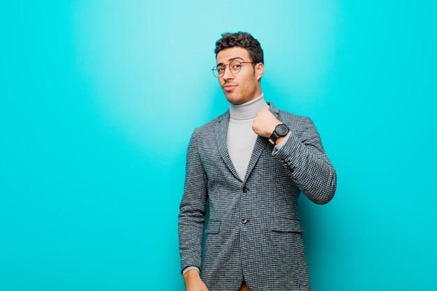 Młody mężczyzna arabski szuka arogancki, udany, pozytywny i dumny, wskazując na siebie o niebieską ścianę