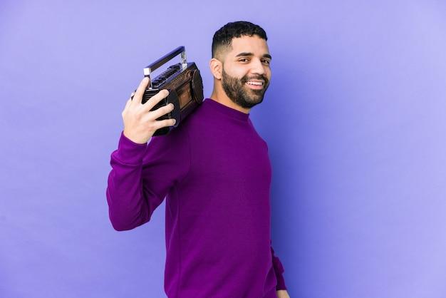 Młody mężczyzna arabskich gospodarstwa izolowane kasety radiowej młody mężczyzna arabski słuchania muzyki wygląda na bok uśmiechnięty, wesoły i przyjemny.