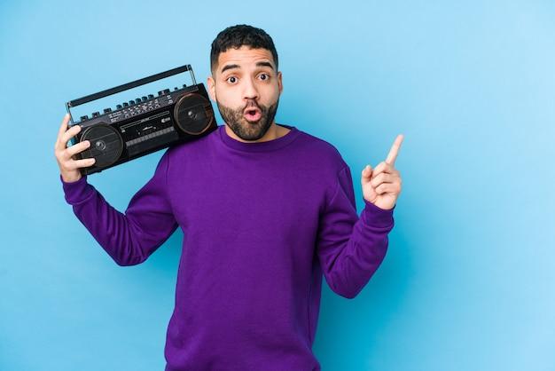 Młody mężczyzna arabskich gospodarstwa kasety radiowej izolowane młody mężczyzna arabskich słuchania muzyki, wskazując na bok
